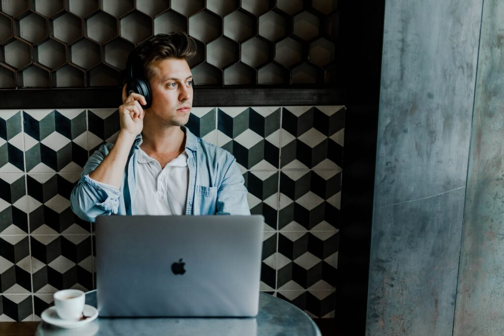 man working remotely with a laptop and headphones