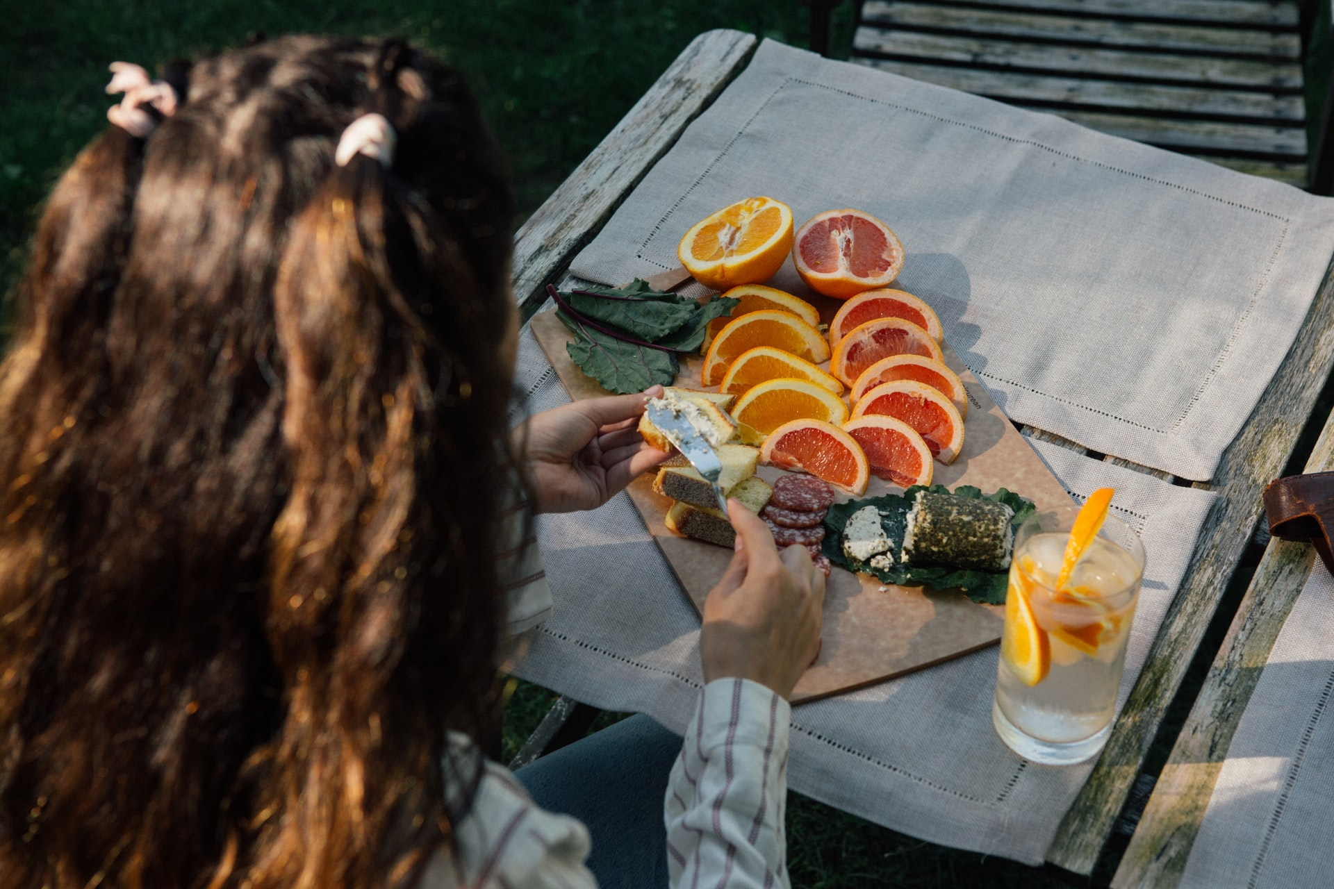 person preparing a cheeseboard with oranges and lemons